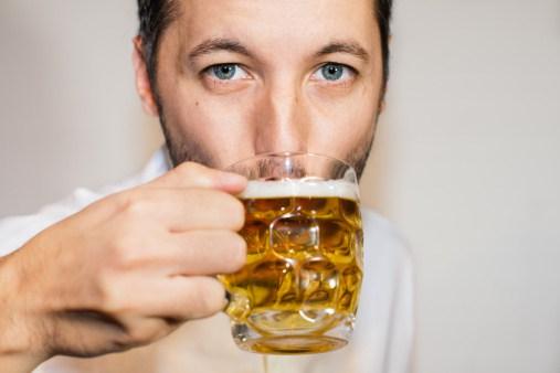 Closeup portrait of blue eyed man drinking beer