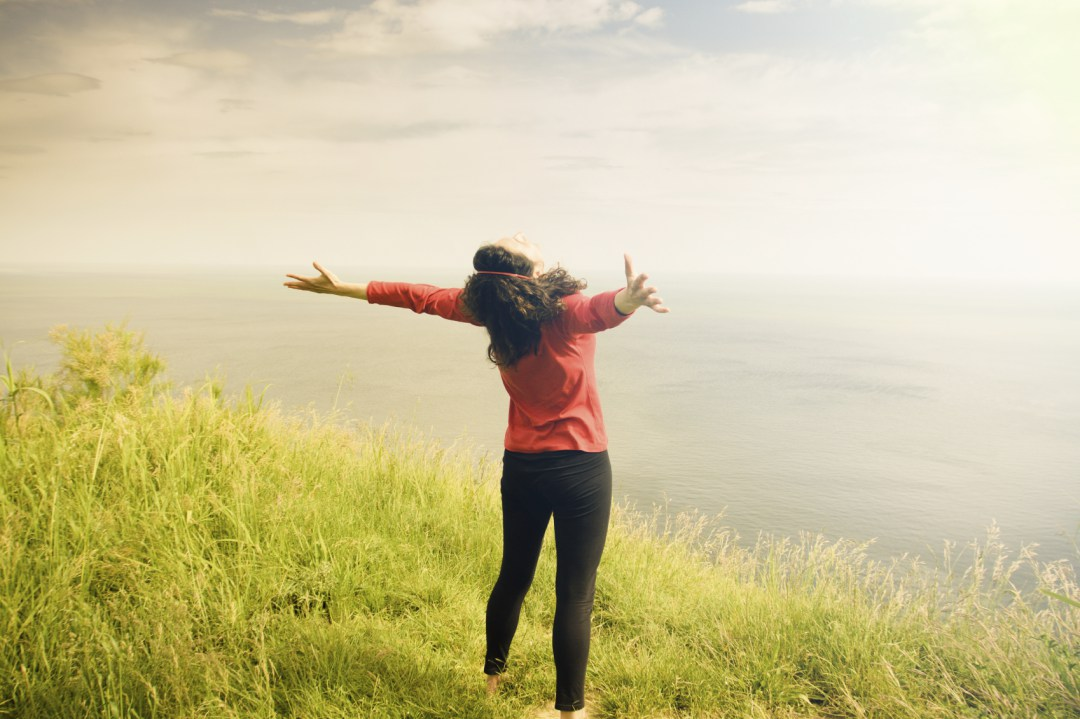 Middle age woman open arms - outdoors location with sea as background, toned image