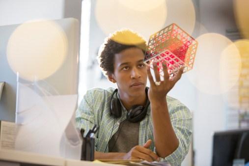 Businessman examining cube at desk in office