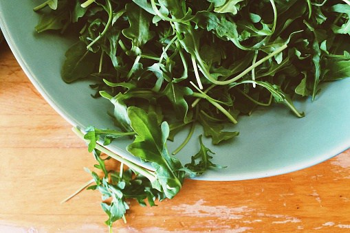 Overhead view of bowl filled with arugula leaves on wooden table with scratches