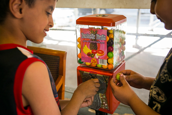 NEW YORK, NY - MAY 15: Two children use a coin operated gum ball machine in the Brooklyn borough of New York. (Photo by Robert Nickelsberg/Getty Images)