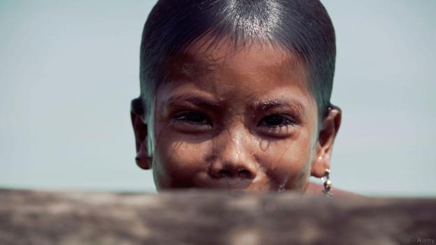 BJN17W Myanmar sea-gypsies, the nomadic hunter-gatherers of South East Asia, a young girl at play in the sea peeks at the camera. Image shot 2007. Exact date unknown.