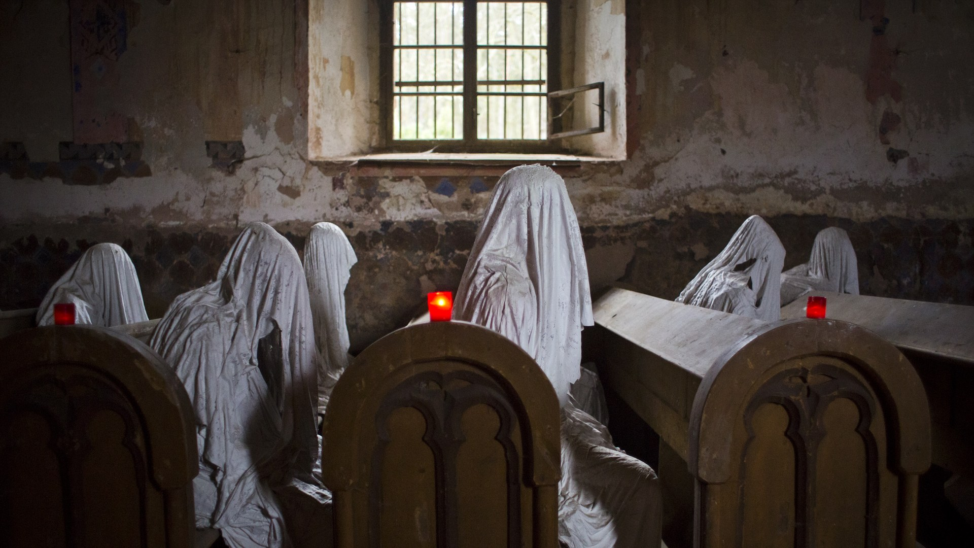 LUKOVA, CZECH REPUBLIC - NOVEMBER 16: Ghost statues by artist Jakub Hadrava are placed at the St. George's church near Plzen on November 16, 2014 in Lukova, Czech Republic. Artist Jakub Hadrava created 32 plaster life-size ghost statues, which symbolize Sudeten Germans who lived in the village. St. George's church, which was build in the north-western Bohemian region of the Czech Republic in 1352, fell into disrepair after the roof collapsed during a funeral service in 1968. Hadrava's aim is to make the church more attractive for visitors and to gain money for renovation work. According to voluntary church manager Petr Koukl, about 2500 people from around the world have been visiting the church this year. (Photo by Matej Divizna/Getty Images)