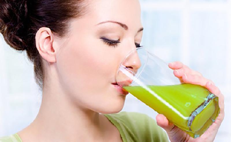 Dievča pitie zeleného šťavy spaľovať tuk